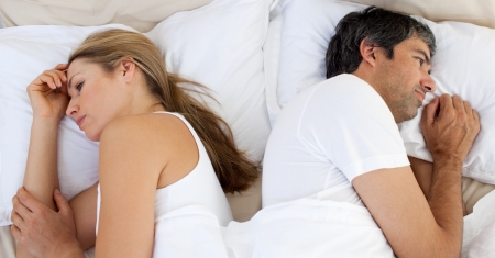 Upset couple sleeping separately photo