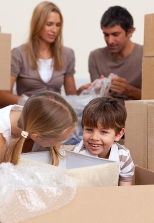 Smiling siblings having fun during house moving photo