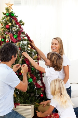 Joyful family decorating Christmas tree  photo