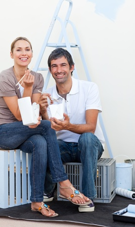 Smiling couple eating while decorating a room photo