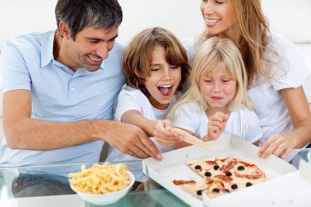 Excited children eating a pizza with their parents photo