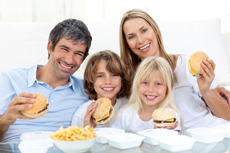 familia comiendo: Familia feliz comiendo hamburguesas sentada en el suelo