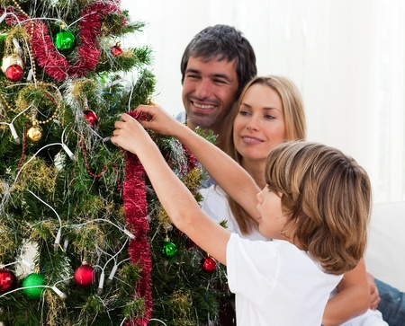 Little boy hanging Christmas decorations with his parents photo