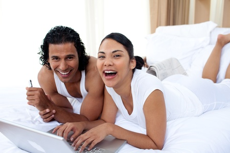 furniture: Couple using a laptop lying on the bed