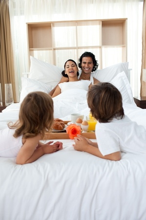breakfasting: Happy family having breakfast lying on the bed