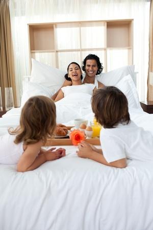 Happy family having breakfast lying on the bed photo