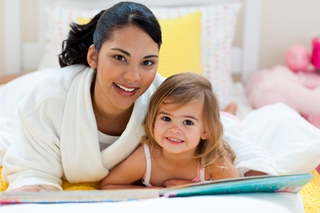 Portrait of a smiling mother and her daughter reading together photo