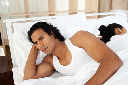 Upset man in bed sleeping separate of a woman Stock Photo - 10097281