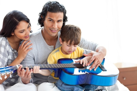 Cute little boy playing guitar with his parents  photo