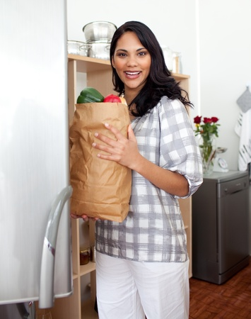 Brunette woman unpacking grocery bag  photo
