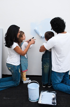 Loving parents helping their children paint photo
