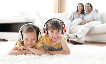 Adorable Geschwister hören Musik mit Kopfhörern