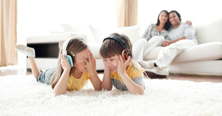 Laughing children listening music with headphones  photo