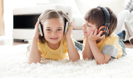 Children playing on the floor with headphones photo