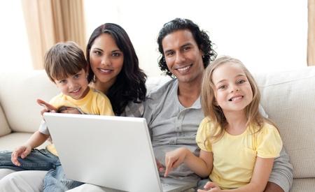 Jolly family using laptop on sofa Stock Photo - 10097297