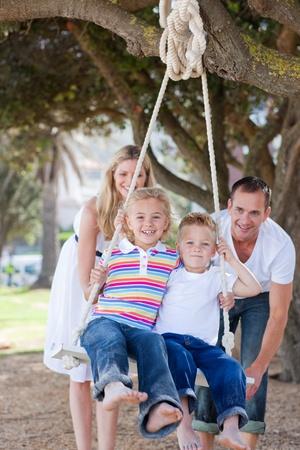 verticales: Felices los padres empujan a sus hijos en un columpio