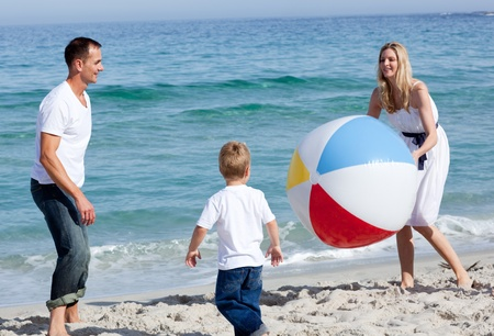 Happy parents and their son playing with a ball  photo