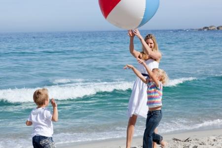 madre e hijo: Feliz madre y sus hijos jugando con una pelota  Foto de archivo