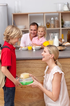 Caring mother packing the school lunch to his son  photo