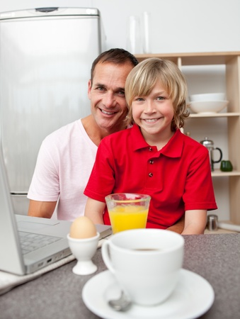 Happy father and his son having breakfast  photo
