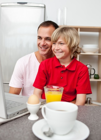 Cheerful father and his son having breakfast Stock Photo - 10096774