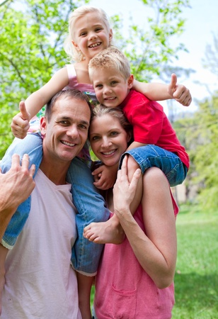 Smiling parents giving their children piggy-back ride Stock Photo - 10097473