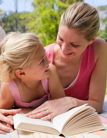 Portrait of a smiling mother and her daughter reading at a picnic photo