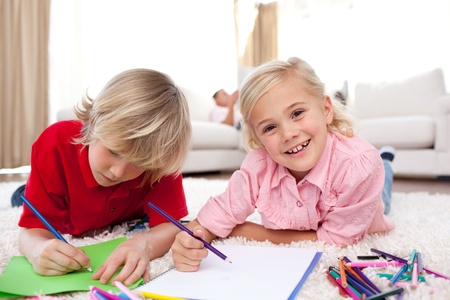 Cheerful children drawing lying on the floor photo