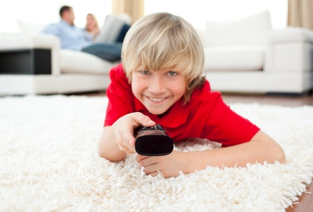Jolly boy watching TV lying on the floor Stock Photo - 10095913