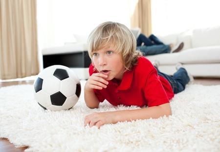 Geanimeerde jongen kijken voetbalwedstrijd op de grond liggen Stockfoto