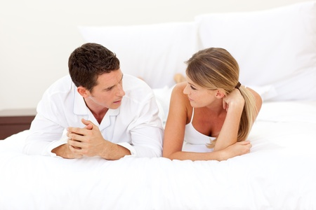 Young couple discussing lying on their bed Stock Photo