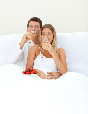 Loving couple drinking Champagne with strawberries  photo