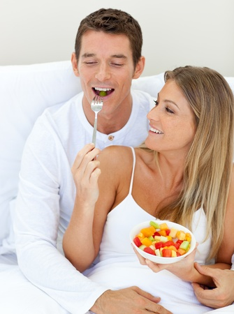 Jolly couple eating fruit lying on their bed  photo