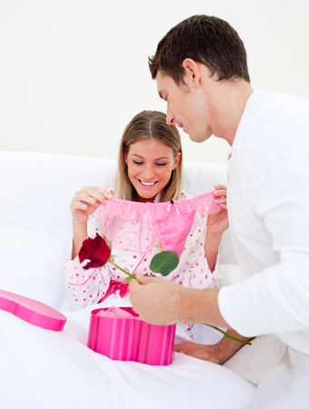 Charming husband giving a present to his wife photo