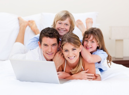 mirthful: Smiling family looking at a laptop lying down on bed