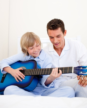 boy playing guitar: Smiling little boy playing guitar with his father Stock Photo