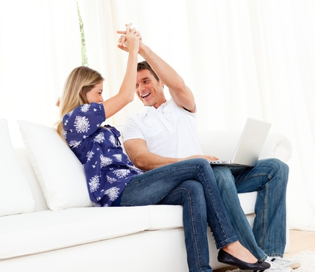 Lively couple using a laptop sitting on sofa photo