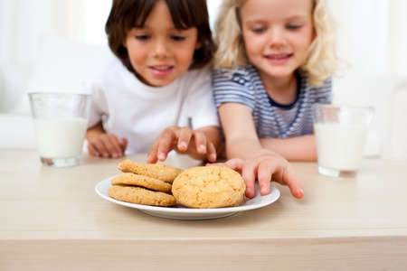 snacking: Adorable siblings eating biscuits