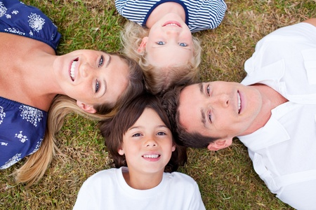 chirpy: Cheerful family lying in circle on the grass