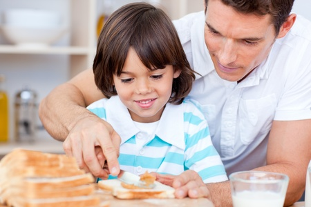 Loving father and his son spreading jam on bread Stock Photo - 10097353