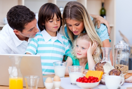 eating breakfast: Happy family using laptop during the breakfast