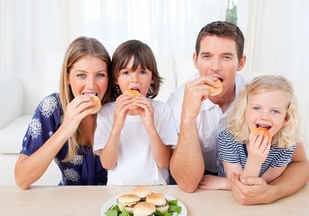 familia comiendo: Familia hambre comer hamburguesas en la sala de estar Foto de archivo