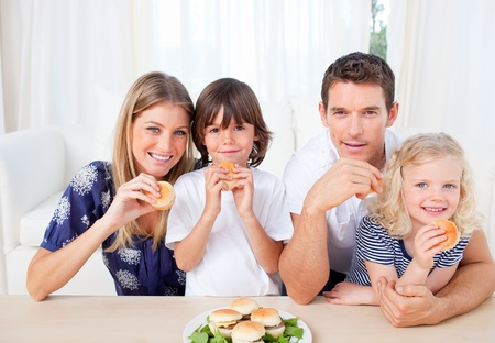 gratified: Smiling family eating burgers in the living room Stock Photo