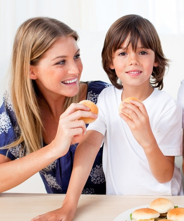 Attractive mother and her son eating burgers  photo