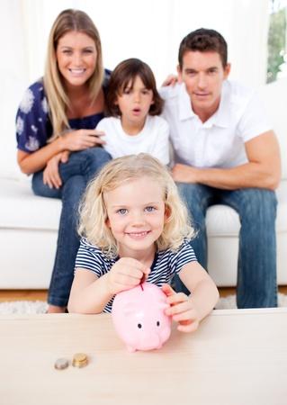 Blond little girl inserting coin in a piggybank photo