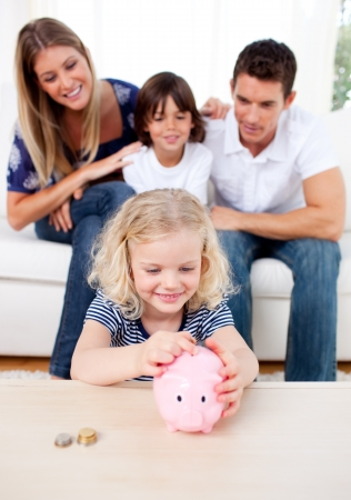 Smiling little girl inserting coin in a piggybank photo