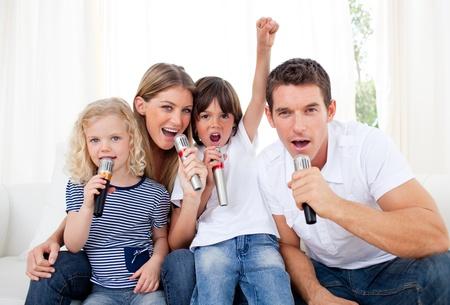 niÑos contentos: Retrato de una alegre cantar familiar a través del micrófono