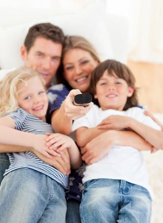 United family watching television sitting on sofa photo