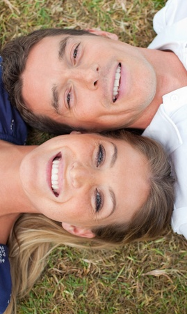 Smiling lovers lying on the grass  photo