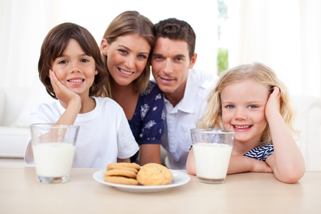 Children eating biscuits and dinking milk with their parents photo